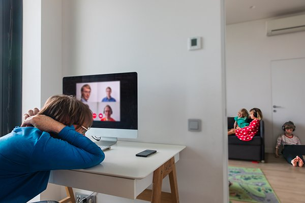 Photo of a person falling asleep during a virtual meeting while kids are on devices in the next room. (Photo courtesy of Getty Images)