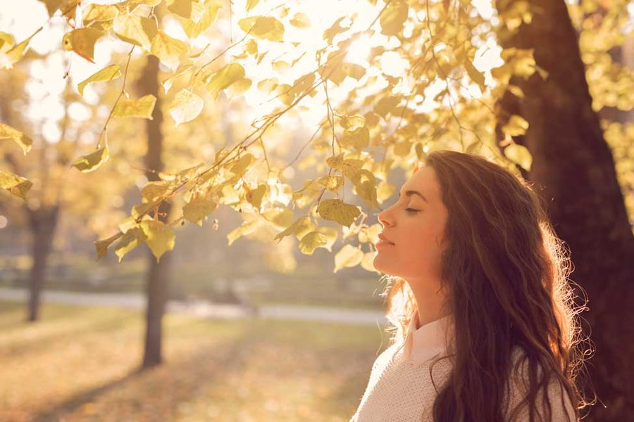 Image of a woman in fall weather, eyes closed, and looking unto s sunset. (Photo by Getty Images)