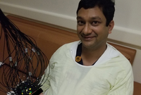 Photo of Manish N. Shah, MD, holding the patient while the Cap-based Transcranial Optical Tomography captures whole-brain imaging in minutes. (Photo credit: Manish N. Shah, MD)