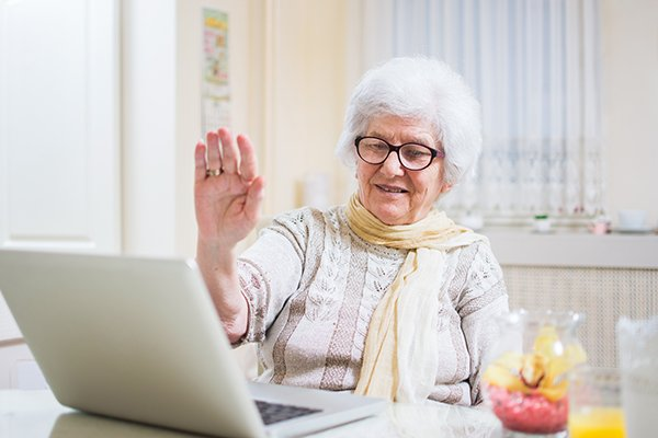 Photo of elderly woman raising her hand in greeting in front of a computer. Photo by Getty Images.