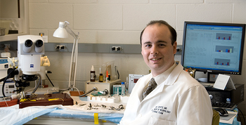 Photo of Dr. Sean Savitz seated in his laboratory. He has been researching stem cells for more than a decade and is the author of a paper published in the journal Stem Cells.