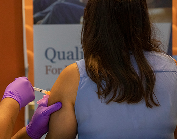 An image of a women receiving a vaccine in her left arm. (Photo by UTHealth).