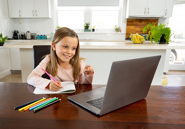 A young girl participating in an online class at home. Photo by Getty Images.