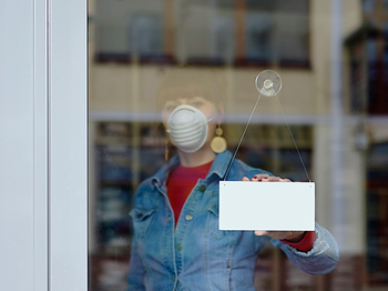 A woman wearing a mask prepares to open up her business. Photo by Getty Images.