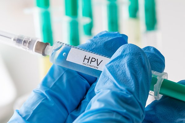 Photo of gloved hand holding syringe loaded with HPV vaccine. Photo from Getty Images.