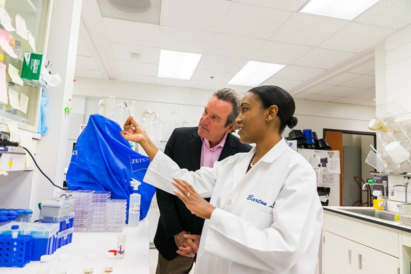 A donor visits a student in the lab