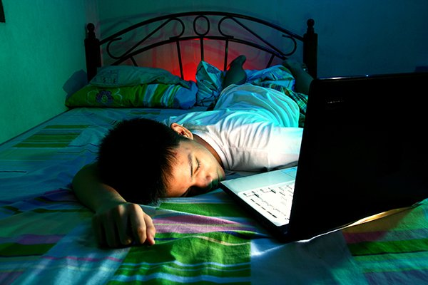 Photo of boy lying on bed asleep in front of a laptop computer. Photo credit is Getty Images.
