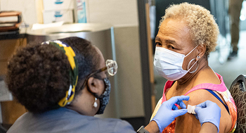 Photo of Beverly Hensley receiving her COVID-19 vaccine from Makita Franklin, RN, at the UTHealth Vaccine Hub. (Photo by Kim Kham, UT Physicians Marketing & Communications)