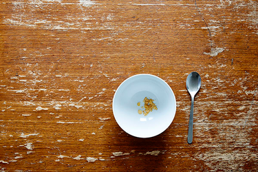 Photo of an empty bowl of cereal with a spoon on a table.