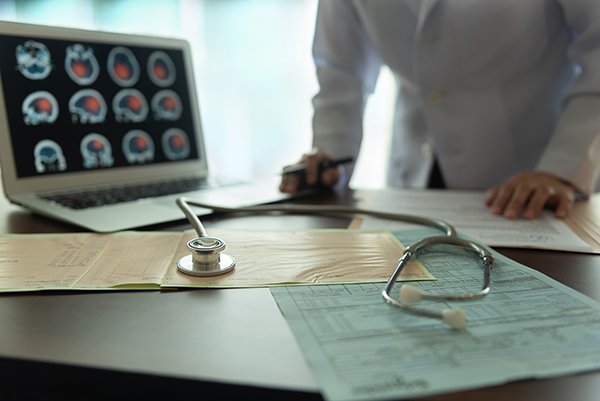 Photo of a screen of brain images and a physician in the background and a stethoscope in the foreground. Photo credit is Getty Images.