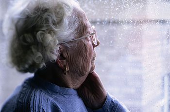 Photo of elderly woman looking out of a window. Photo credit is Getty Images