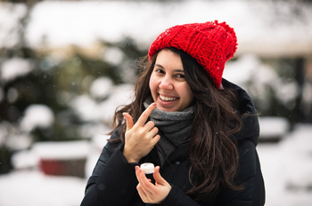 Image of young woman applying cream to lips in cold weather outdoors. (Photo credit: Getty Images)