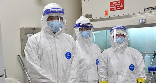 Photo of Victor Guaregua; Xiaoyi Yuan, PhD; and Yanyu Wang, PhD; wearing full PPE and standing inside the BSL-3 laboratory. (Photo by Dwight Andrews/UTHealth)