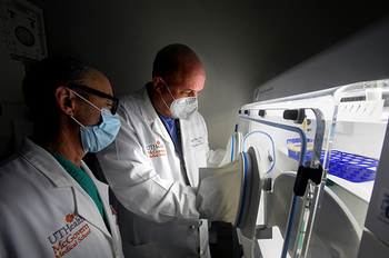 Photo of Ben Bobrow, MD, and Holger Eltzschig, MD, PhD, using the hypoxia chamber, which helped them discover that HIF activators could potentially treat damaged lungs. (Photo credit: Cody Duty/UTHealth)