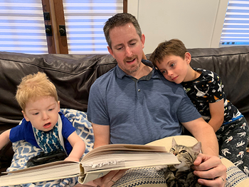 Nathan Hoot, MD, PhD, reads to his two sons on the couch.