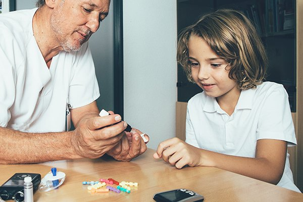 Image of father showing child how to check his blood sugar (Photo by: Getty Images)