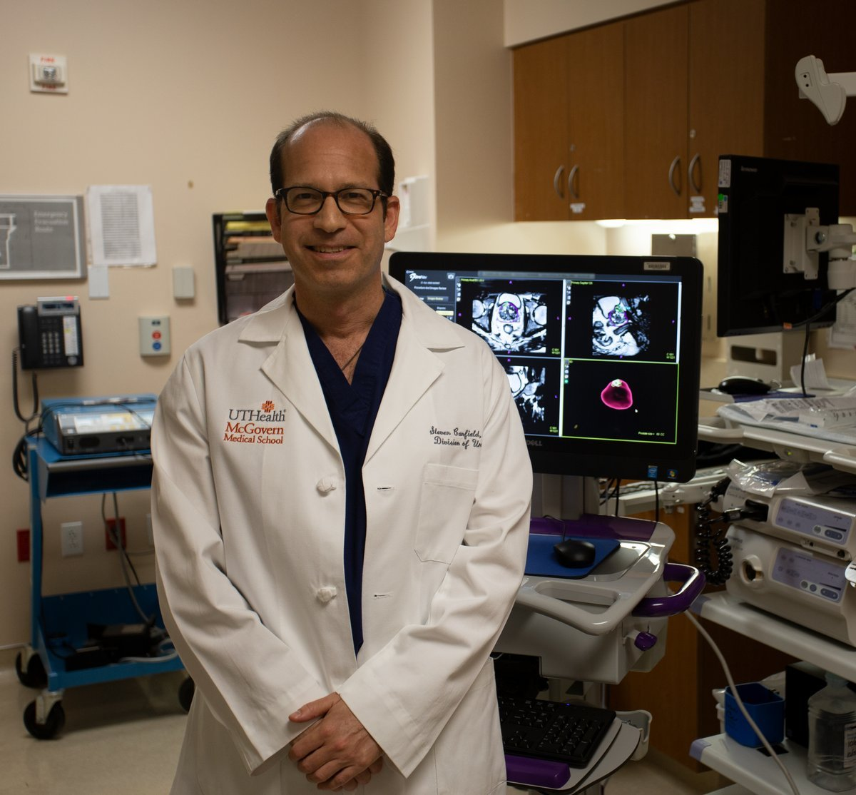 Photo of Steven Canfield, M.D.. Behind him in the photo is the advanced imaging results he uses to identify and diagnose the cancer. PHOTO CREDIT: UTHealth
