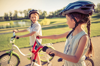 Photo of a boy and a girl on their bicycles. Photo credit is Getty Images.