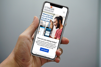Photo of hand holding a phone showing digital cognitive therapy landing page