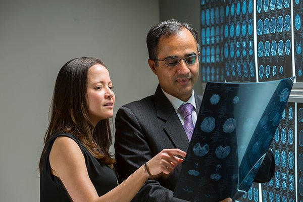 Photo of study lead author Nitin Tandon, MD, professor in the Vivian L. Smith Department of Neurosurgery at McGovern Medical School and co-author Jessica Johnson, BSN, nurse practitioner reviewing brain scans. Photo credit is Memorial Hermann