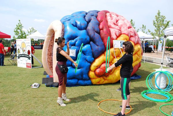 Photo of two women holding hula hoops in front of inflatable brain at the UTHealth Stomp Out Stroke Festival.