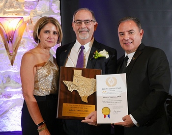 Photo of UTHealth School of Dentistry Dean John Valenza, DDS, receiving 2019 Texas Dentist of the Year award. He is pictured with his wife, Debbie Valenza, and 2018  winner Jose Cazares, DDS. (Photo by Taylor LeBlanc)