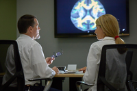 Researchers reviewing brain scans on a large screen in a meeting room. (Photo by Terry Vine Photography)