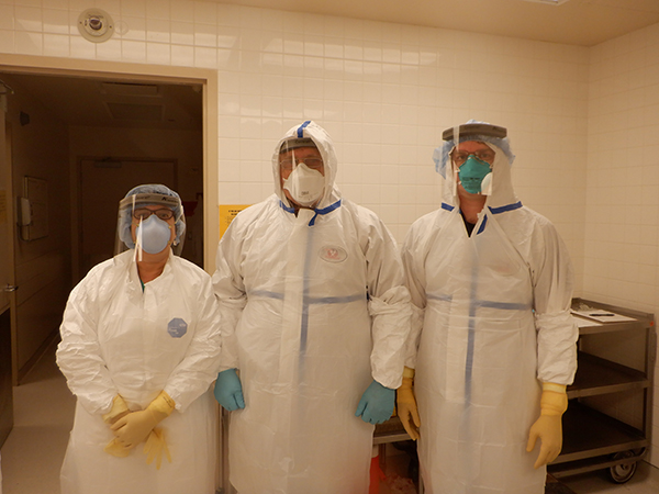 From left to right: Meena Bhattacharjee, MD, L. Maximilian Buja, MD, and Noah Reilly, DO in PPE before an autopsy. (Photo Credit: Rongzhen Zhang, MD)