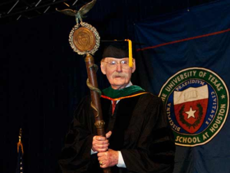 Dr. Duke holding the cerimonial mace at graduation or our UTHealth medical school students.